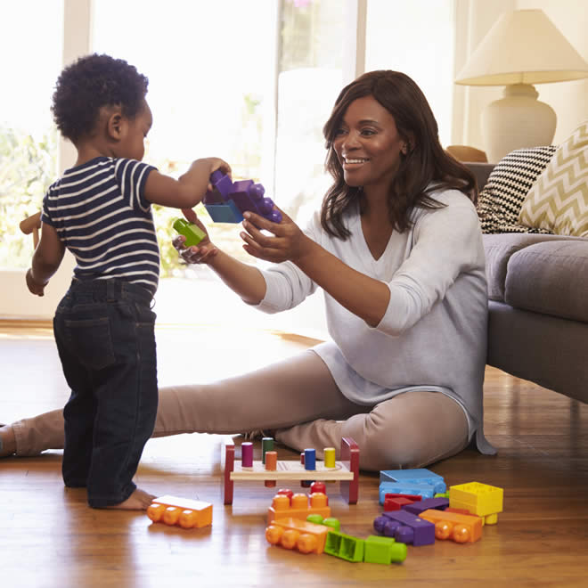 mother and son playing with blocks on hardwood floors
