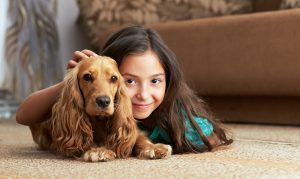 girl and dog laying on carpet floor