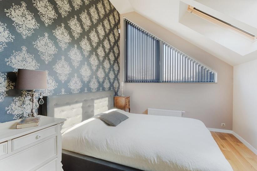 Bedroom with fancy design wallpaper and wood floors